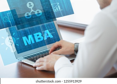 Business, technology, internet and networking concept. Young businessman working on his laptop in the office, select the icon MBA on the virtual display.