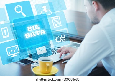 Business, technology, internet and networking concept. Young businessman working on his laptop in the office, select the icon big data on the virtual display.