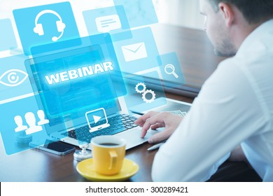 Business, technology, internet and networking concept. Young businessman working on his laptop in the office, select the icon webinar on the virtual display.