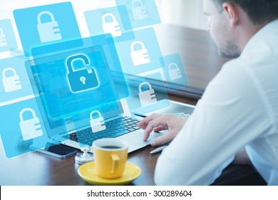 Business, technology, internet and networking concept. Young businessman working on his laptop in the office, select the icon digital security on the virtual display.