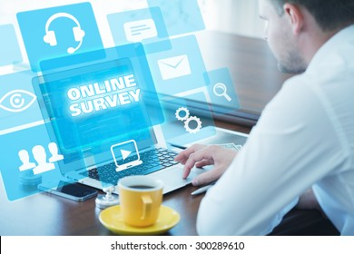 Business, technology, internet and networking concept. Young businessman working on his laptop in the office, select the icon online survey on the virtual display.