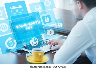 Business, technology, internet and networking concept. Young businessman working on his laptop in the office, select the icon value-added tax on the virtual display.