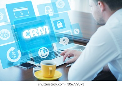 Business, technology, internet and networking concept. Young businessman working on his laptop in the office, select the icon CRM â?? Customer Relationship Management on the virtual display.