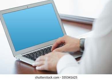 Business, technology, internet and networking concept. Young male businessman sitting at a desk in the office.