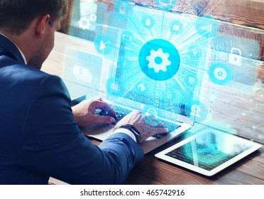 Business, technology, internet and networking concept. Young businessman working on his laptop in the office, select the icon automation on the virtual display.