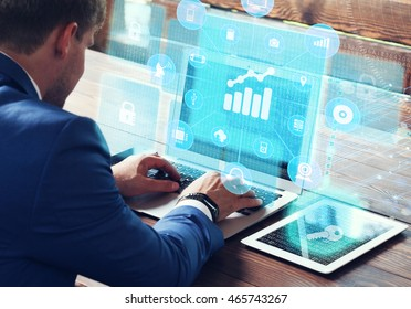 Business, technology, internet and networking concept. Young businessman working on his laptop in the office, select the icon Financial charts on the virtual display.
