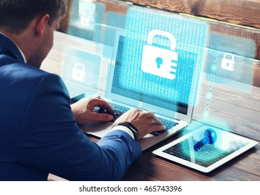 Business, technology, internet and networking concept. Young businessman working on his laptop in the office, select the icon security on the virtual display.
