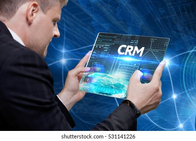 Business, technology, internet and networking concept. Young businessman working on his laptop in the office, select the icon CRM on the virtual display.