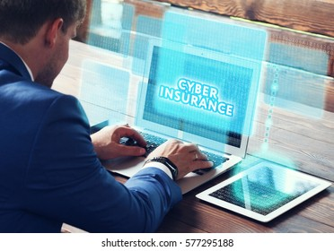 Business, technology, internet and networking concept. Young businessman working on his laptop in the office, select the icon Cyber insurance on the virtual display.