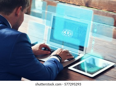 Business, technology, internet and networking concept. Young businessman working on his laptop in the office, select the icon API on the virtual display.