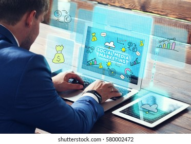 Business, technology, internet and networking concept. Young businessman working on his laptop in the office, select the icon Social media marketing on the virtual display.