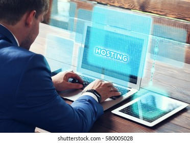 Business, technology, internet and networking concept. Young businessman working on his laptop in the office, select the icon Hosting on the virtual display.