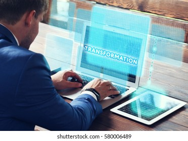 Business, technology, internet and networking concept. Young businessman working on his laptop in the office, select the icon Transformation on the virtual display.