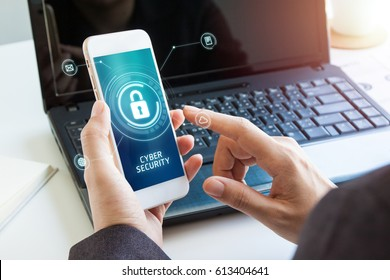 Business, technology, internet and networking concept. businessman working on his laptop and mobile in the office select the icon security on the virtual display. Cyber security