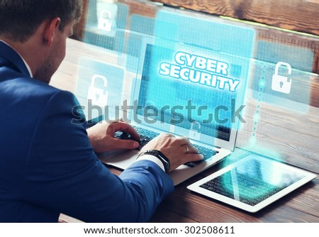 Business, technology, internet and networking concept. Young businessman working on his laptop in the office, select the icon cyber security on the virtual display.