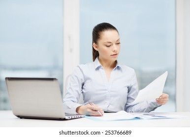 business, technology, internet and office concept - busy, businesswoman with laptop and charts in office