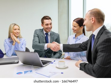 business, technology and office concept - two smiling businessman shaking hands in office