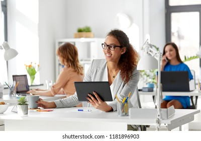 business, technology and people concept - african american businesswoman with tablet pc computer drinking coffee at office