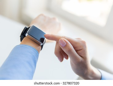 business, technology and people concept - close up of woman hands setting smart watch at office