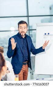 business, technology, people, deadline and team work concept - smiling male boss talking to business group at office background