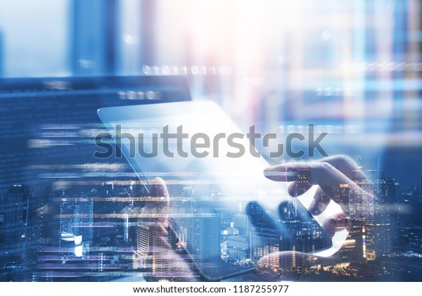 Business and technology, software development, IoT concept. Double exposure, man programmer, software developer working on digital tablet and smart city with binary, html computer code on screen