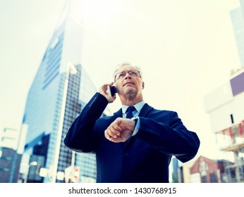 business, technology, time, punctuality and people concept - senior businessman calling on smartphone with wristwatch or smart watch on his hand in city