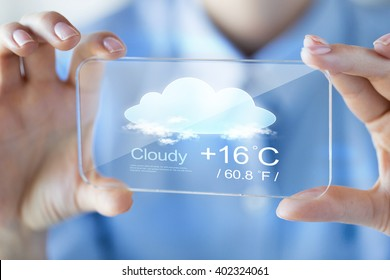 business, technology, weather cast and people concept - close up of woman hand holding and showing transparent with forecast screen smartphone at office