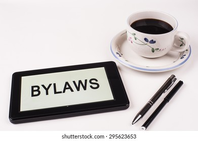 Business Term / Phrase on Tablet PC with a cup of coffee and pens on a White Background - Black Word(s) on a white background - Bylaws