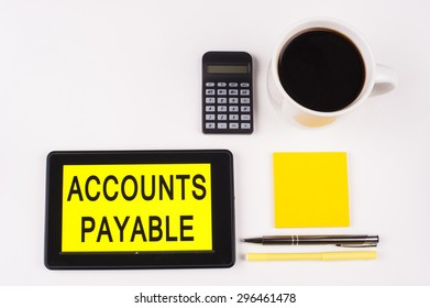Business Term / Business Phrase on Tablet PC with a cup of coffee, Pens, Calculator, and yellow note pad on a White Background - Black Word(s) on a yellow background - Accounts Payable