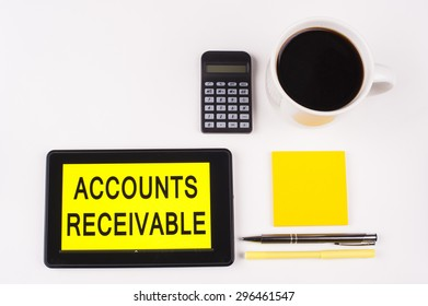 Business Term / Business Phrase on Tablet PC with a cup of coffee, Pens, Calculator, and yellow note pad on a White Background - Black Word(s) on a yellow background - Accounts Receivable