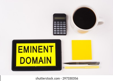 Business Term / Business Phrase on Tablet PC with a cup of coffee, Pens, Calculator, and yellow note pad on a White Background - Black Word(s) on a yellow background - Eminent Domain