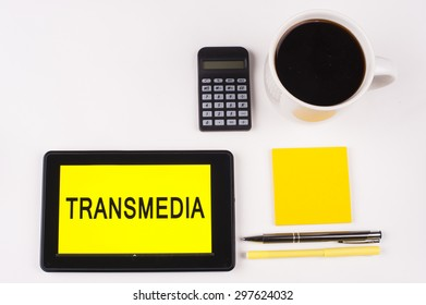 Business Term / Business Phrase on Tablet PC with a cup of coffee, Pens, Calculator, and yellow note pad on a White Background - Black Word(s) on a yellow background - Transmedia