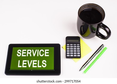 Business Term / Business Phrase on Tablet PC - Cup of coffee, Pens, Calculator and a green/yellow note pad on a White surface - White Word(s) on a green background - Service Levels