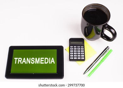 Business Term / Business Phrase on Tablet PC - Cup of coffee, Pens, Calculator and a green/yellow note pad on a White surface - White Word(s) on a green background - Transmedia