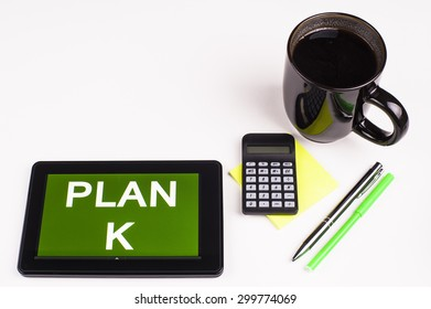 Business Term / Business Phrase on Tablet PC - Cup of coffee, Pens, Calculator and a green/yellow note pad on a White surface - White Word(s) on a green background - Plan K