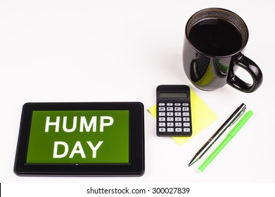 Business Term / Business Phrase on Tablet PC - Cup of coffee, Pens, Calculator and a green/yellow note pad on a White surface - White Word(s) on a green background - Hump Day