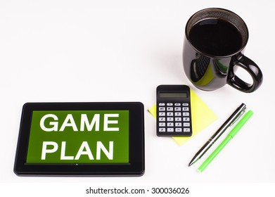 Business Term / Business Phrase on Tablet PC - Cup of coffee, Pens, Calculator and a green/yellow note pad on a White surface - White Word(s) on a green background - Game Plan