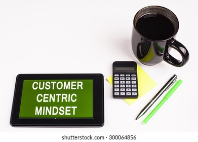 Business Term / Business Phrase on Tablet PC - Cup of coffee, Pens, Calculator and a green/yellow note pad on a White surface - White Word(s) on a green background - Customer Centric Mindset