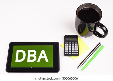 Business Term / Business Phrase on Tablet PC - Cup of coffee, Pens, Calculator and a green/yellow note pad on a White surface - White Word(s) on a green background - DBA