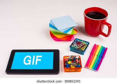 Business Term / Business Phrase on Tablet PC - Colorful Rainbow Colors, Cup, Notepad, Pens, Paper Clips, White surface - White Word(s) on a cyan background - Gif
