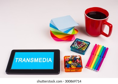 Business Term / Business Phrase on Tablet PC - Colorful Rainbow Colors, Cup, Notepad, Pens, Paper Clips, White surface - White Word(s) on a cyan background - Transmedia