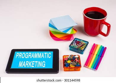 Business Term / Business Phrase on Tablet PC - Colorful Rainbow Colors, Cup, Notepad, Pens, Paper Clips, White surface - White Word(s) on a cyan background - Programmatic Marketing