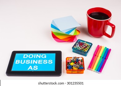 Business Term / Business Phrase on Tablet PC - Colorful Rainbow Colors, Cup, Notepad, Pens, Paper Clips, White surface - White Word(s) on a cyan background - Doing Business As