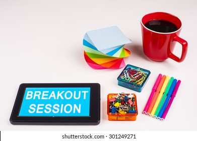Business Term / Business Phrase on Tablet PC - Colorful Rainbow Colors, Cup, Notepad, Pens, Paper Clips, White surface - White Word(s) on a cyan background - Breakout Session