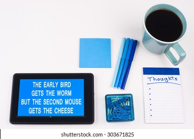 Business Term / Business Phrase on Tablet PC - Blue Colors, Coffee, Pens, Paper Clips and note pads on White - White Word(s) on blue - The Early Bird Gets The Worm But The Second Mouse Gets The Cheese