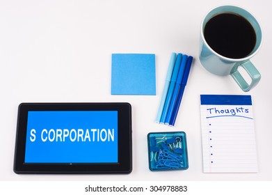 Business Term / Business Phrase on Tablet PC - Blues, cup of coffee, Pens, paper clips Calculator with a blue note pad on White - White Word(s) on blue - S Corporation