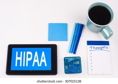Business Term / Business Phrase on Tablet PC - Blue Colors, Coffee, Pens, Paper Clips and note pads on White - White Word(s) on blue - HIPAA