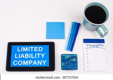 Business Term / Business Phrase on Tablet PC - Blue Colors, Coffee, Pens, Paper Clips and note pads on White - White Word(s) on blue - Limited Liability Company