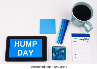 Business Term / Business Phrase on Tablet PC - Blue Colors, Coffee, Pens, Paper Clips and note pads on White - White Word(s) on blue - Hump Day