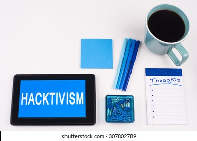 Business Term / Business Phrase on Tablet PC - Blues, cup of coffee, Pens, paper clips Calculator with a blue note pad on White - White Word(s) on blue - Hacktivism